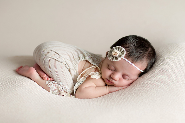 newborn photo of Stella in romper in the pillow pose in studio