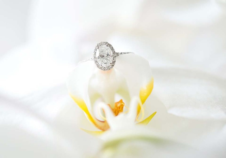 bridal engagement ring photo placed on white orchid floral bridal bouquet