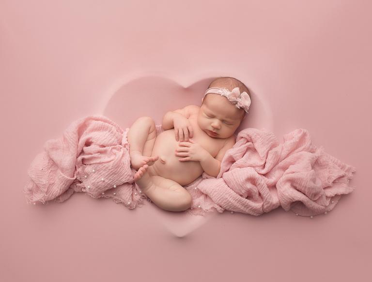 newborn photo of Stella in romper in the pillow pose in studio